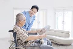 Enfermeira fêmea que fala com ancião em casa imagens de stock