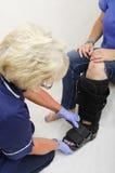 Enfermeira Fitting uma bota ortopédica a uma senhora com um pé quebrado Foto de Stock