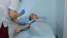 Enfermeira hábil que põe o conta-gotas a um paciente fêmea que encontra-se sobre uma cama de hospital Foto de Stock Royalty Free