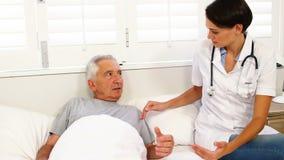 Enfermeira home que fala com o paciente idoso video estoque
