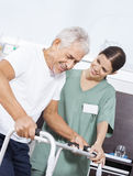 Enfermeira Looking At Senior Walker In Rehab Center de utilização paciente Fotografia de Stock Royalty Free