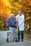 Enfermeira masculina que ajuda ao paciente superior com o caminhante no parque imagens de stock