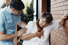 Enfermeira masculina que ajuda a mulher idosa com dor no peito imagens de stock royalty free