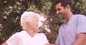 Enfermeira masculina que ajuda a uma mulher superior a andar no quintal video estoque
