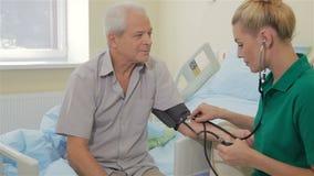 A enfermeira mede a pressão sanguínea do paciente masculino vídeos de arquivo
