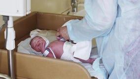 A enfermeira no roupão envolve o bebê recém-nascido com os braceletes azuis nas mãos no hospital de maternidade video estoque