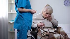 Enfermeira nova que d? medicamenta??es ? senhora idosa na cadeira de rodas, centro de reabilita??o fotografia de stock royalty free