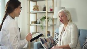 Enfermeira nova que usa a tabuleta e visitando a mulher saudável da aposentadoria filme