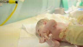 A enfermeira pôs bebê apenas-nascido sobre uma tabela video estoque
