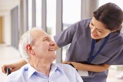 Enfermeira Pushing Senior Patient na cadeira de rodas ao longo do corredor Fotografia de Stock Royalty Free