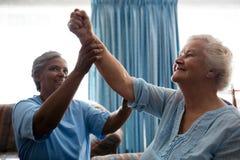 Enfermeira que ajuda a mulher superior em dobrar os músculos imagem de stock