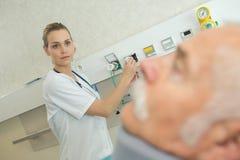 Enfermeira que ajusta o ajuste para a necessidade dos pacientes Imagem de Stock Royalty Free