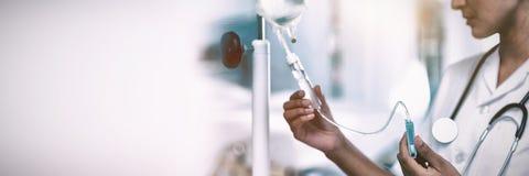 Enfermeira que conecta um gotejamento intravenoso foto de stock