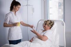 Enfermeira que dá a medicina ao paciente Imagem de Stock Royalty Free