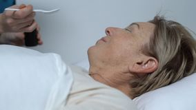 Enfermeira que dá o xarope ao paciente fêmea idoso que encontra-se na cama, tratamento de hospital vídeos de arquivo
