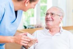 Enfermeira que dá medicamentos de venta com receita do homem superior Fotografia de Stock Royalty Free