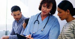 Enfermeira que discute um relatório médico com a mulher filme