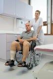 Enfermeira que empurra o homem superior dos enfermos no hospital Imagens de Stock