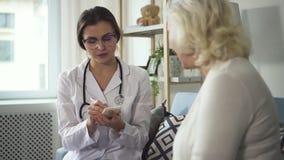 Enfermeira que escreve a prescrição para medicinas à mulher aposentada video estoque