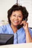 Enfermeira que faz o telefonema na estação das enfermeiras foto de stock royalty free