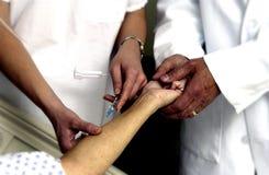 Enfermeira que setting-up um IV Fotografia de Stock Royalty Free