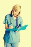 Enfermeira que toma notas fotografia de stock