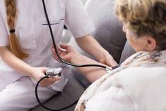 Enfermeira que toma a pressão do paciente fotografia de stock royalty free
