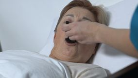 Enfermeira que trata a mulher adulta com o xarope, paciente fêmea que encontra-se na cama de hospital filme