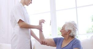 Enfermeira que verifica o braço da mulher superior video estoque