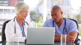 Enfermeira séria que fala com um doutor na frente de um portátil vídeos de arquivo