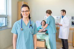 Enfermeira Smiling With Patient e Team In médico foto de stock royalty free