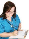 A enfermeira toma notas fotografia de stock