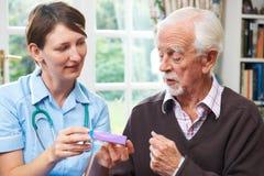 Enfermera Advising Senior Man en la medicación en casa Foto de archivo