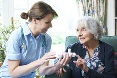 Enfermera Advising Senior Woman en la medicación en casa Foto de archivo libre de regalías