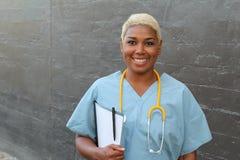 Enfermera afroamericana feliz joven que se coloca en la sala de hospital con el tablero y la pluma a disposición Sonrisa, mirando fotos de archivo libres de regalías