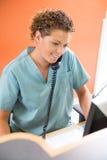 Enfermera Answering Telephone While que trabaja en Fotos de archivo libres de regalías