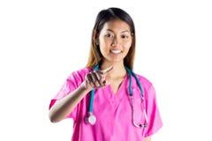 Enfermera asiática con el estetoscopio que señala delante de ella Imagen de archivo libre de regalías
