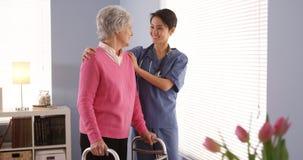 Enfermera asiática y ventana que hace una pausa paciente mayor Imagen de archivo