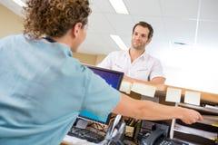 Enfermera Assisting Man While que trabaja en la recepción Imagenes de archivo