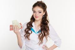 Enfermera bonita con las píldoras aisladas en blanco Imagen de archivo libre de regalías
