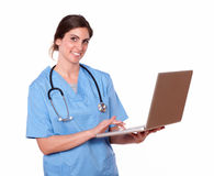 Enfermera bonita que sonríe mientras que usa su ordenador portátil Imagen de archivo libre de regalías