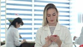 Enfermera bonita que usa el móvil mientras que otro mostrador de recepción de la limpieza de la enfermera almacen de video