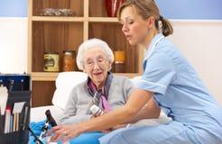 Enfermera BRITÁNICA que visita a la mujer mayor en el país imagen de archivo