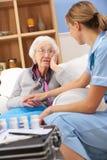 Enfermera BRITÁNICA que visita a la mujer mayor en el país fotos de archivo
