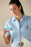 Enfermera BRITÁNICA que lleva a cabo el paquete del medicamento de venta con receta Fotografía de archivo libre de regalías