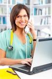 Enfermera con el teléfono y la computadora portátil foto de archivo