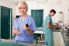 Enfermera con la jeringuilla mientras que informe de la escritura del doctor imágenes de archivo libres de regalías