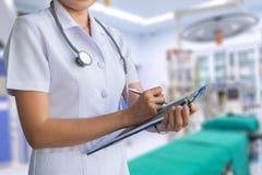 Enfermera de la mujer en el informe blanco de la capa en un cuaderno en el fondo de la falta de definición de la sala de operacio Foto de archivo