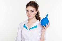 Enfermera de los jóvenes con el enema azul en manos Fotos de archivo