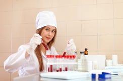 Enfermera con el tubo de ensayo en laboratorio Fotos de archivo libres de regalías